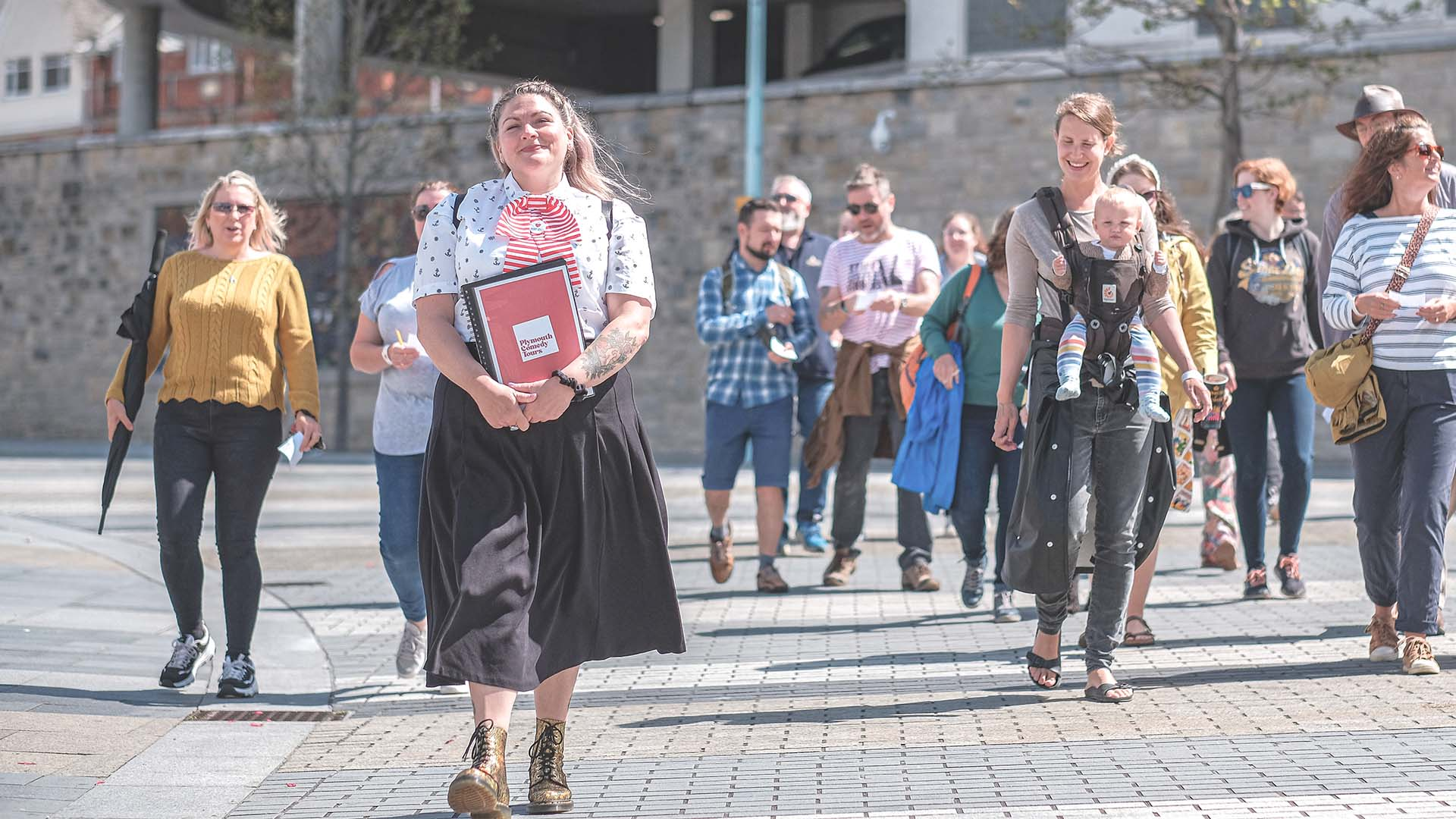 Plymouth Comedy Tours guide Suzy Bennett leading a group of happy tourists.